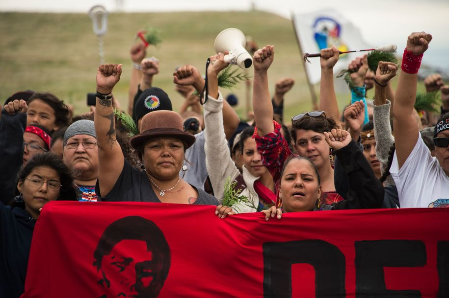 "Native Americans march to a burial ground sacred site that was disturbed by bulldozers building the Dakota Access Pipeline (DAPL), near the encampment where hundreds of people have gathered to join the Standing Rock Sioux Tribe's protest of the oil pipeline that is slated to cross the Missouri River nearby, September 4, 2016 near Cannon Ball, North Dakota. / AFP / Robyn BECK / TO GO WITH AFP STORY by Nova SAFO, ""Native Americans united by oil pipeline fight"" (Photo credit should read ROBYN BECK/AFP/Getty Images)"