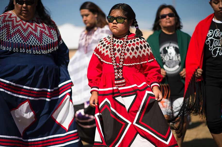 Women and girls from the Colorado River Indian tribes dance after arriving at a protest encampment near Cannon Ball, North Dakota to lend their support to the Standing Rock Sioux Tribe's opposition to the Dakota Access Pipeline (DAPL) September 3, 2016..Drive on a state highway along the Missouri River, amid the rolling hills and wide prairies of North Dakota, and you'll come across a makeshift camp of Native Americans -- united by a common cause. Members of some 200 tribes have gathered here, many raising tribal flags that flap in the unforgiving wind. Some have been here since April, their numbers fluctuating between hundreds and thousands, in an unprecedented show of joint resistance to the nearly 1,200 mile-long Dakota Access oil pipeline. / AFP / Robyn BECK (Photo credit should read ROBYN BECK/AFP/Getty Images)